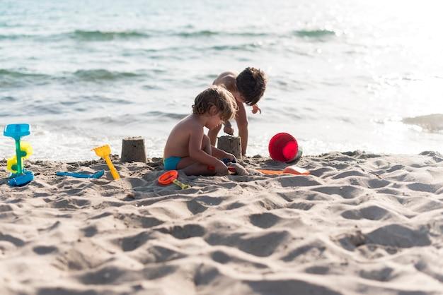 Hermanos de tiro largo haciendo castillos de arena en la playa