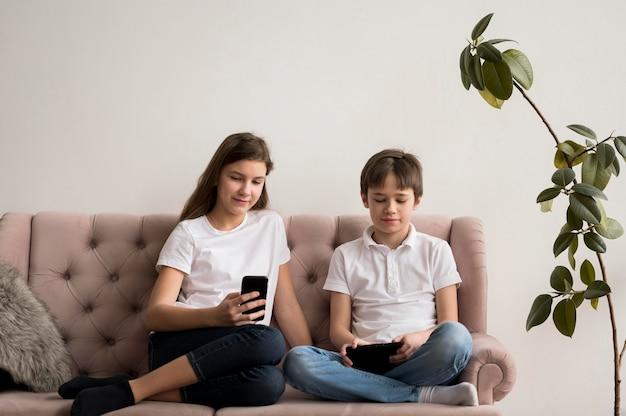 Hermanos usando móvil y mesa
