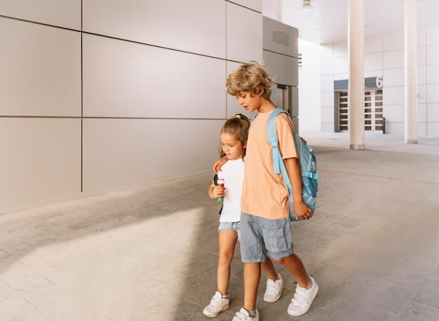Los hermanos van a la escuela con sus mochilas y un balón de fútbol.