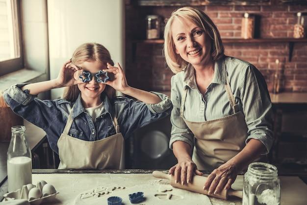 Hermosa abuela y nieta están cortando galletas.