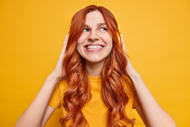 Hermosa adolescente despreocupada sonríe ampliamente disfruta de su música favorita en auriculares inalámbricos estéreo tiene el pelo largo y pelirrojo pasa tiempo libre disfrutando de la lista de reproducción