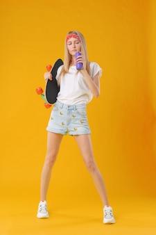 Hermosa y adolescente de moda posando con una patineta en estudio