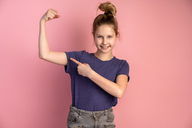 Hermosa adolescente muestra sus músculos en una pared rosa