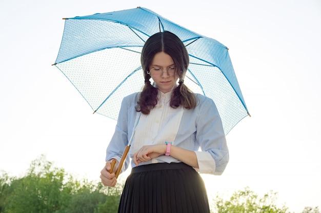 Hermosa adolescente con un paraguas mira el reloj de pulsera