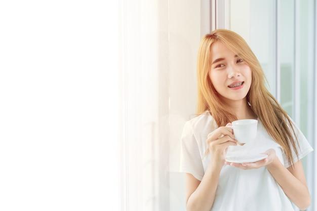 Hermosa adolescente de pie sosteniendo la taza de café bebida caliente relajarse en las ventanas de la oficina