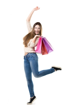 Hermosa adolescente saltando de alta con el placer de celebración bolsas de compras de color rosa
