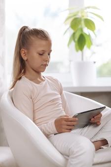 Hermosa adolescente sentada en un sillón blanco en la habitación blanca haciendo los deberes con tableta