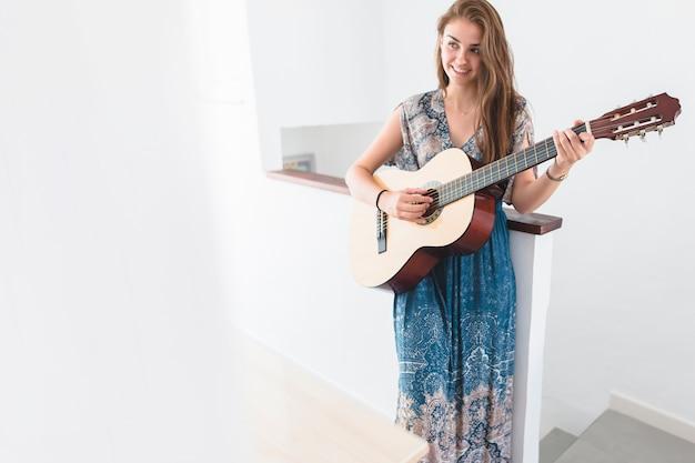Hermosa adolescente tocando la guitarra en casa