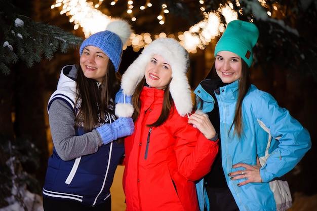 Hermosa alegre amiga en coloridas chaquetas divirtiéndose y caminando en la calle de la ciudad por la noche en navidad.