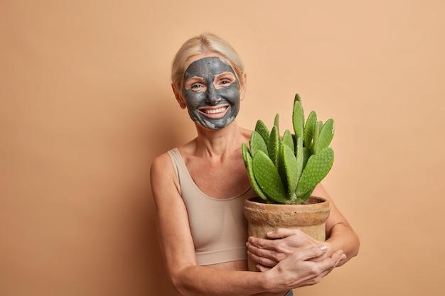 Hermosa y alegre mujer europea de cuarenta años aplica una máscara de belleza para reducir las arrugas tiene una expresión positiva viste una parte superior recortada lleva poses de cactus en macetas en el interior
