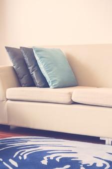 Hermosa almohada de lujo en la decoración del sofá en el interior de la sala de estar - vintage light filter