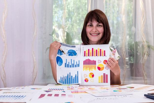 Hermosa analista con gráficos de negocios en office