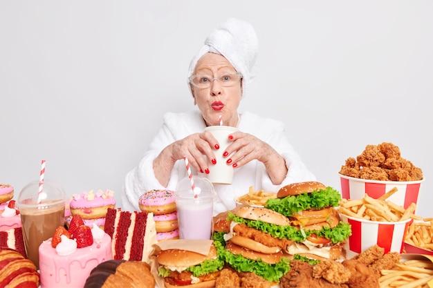 Hermosa anciana bebe bebidas gaseosas come alimentos con alto contenido de grasa y azúcar tiene una ración desequilibrada de nutrición malsana