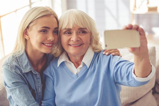 Hermosa anciana y joven están haciendo selfie.