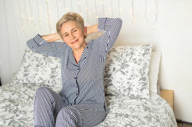 Hermosa anciana en pijama en la cama