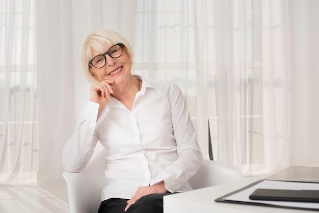 Hermosa anciana sentada en su oficina