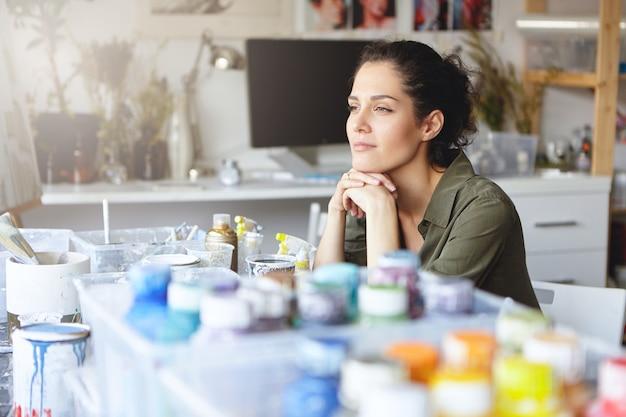 Hermosa artista femenina con expresión pensativa, sentada en su lugar de trabajo con acuarelas, tratando de imaginar la imagen que ella va a pintar. gente, hobby, creatividad, concepto de pintura