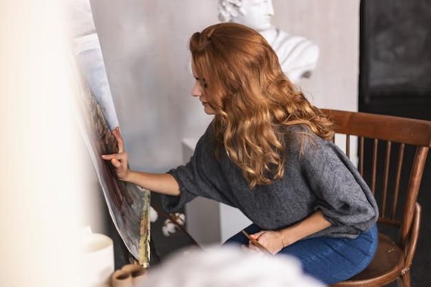 Hermosa artista femenina trabajando en un proyecto de arte en su estudio.