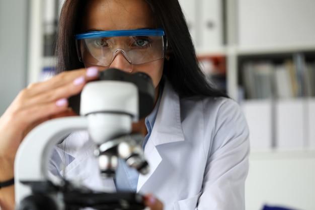 Hermosa asistencia madura usando microscopio científico