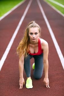 Hermosa atleta en una pista de carreras está lista para correr