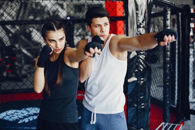 Una hermosa y atlética chica de ropa deportiva entrenando en el gimnasio con su novio