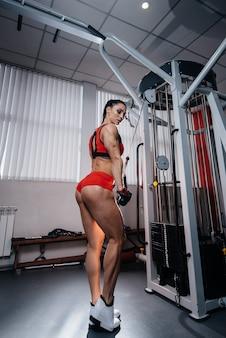 Una hermosa y atlética chica sexy entrena y hace ejercicio en el gimnasio.