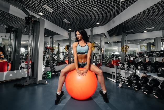 Una hermosa y atlética chica sexy está sentada sobre una pelota después de las clases de gimnasia en el gimnasio. fitness, culturismo.