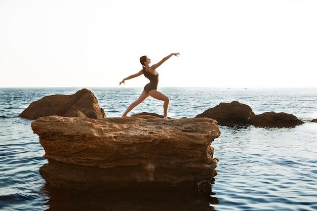 Hermosa bailarina bailando, posando en roca en la playa, vistas al mar.