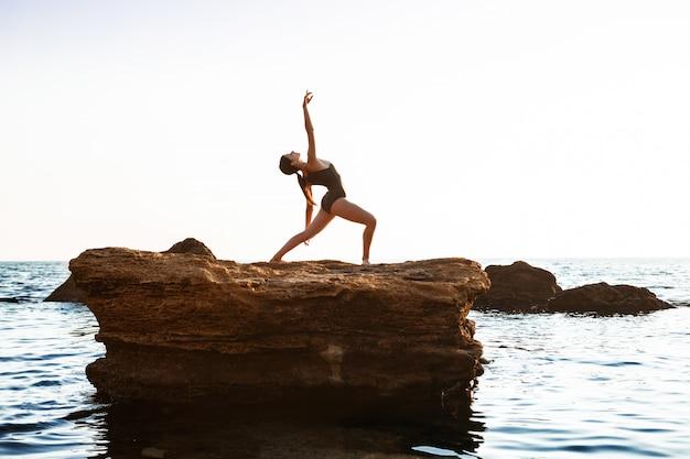 Hermosa bailarina bailando, posando en roca en la playa