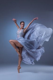 Hermosa bailarina bailando en vestido largo azul sobre fondo azul.
