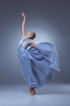 La hermosa bailarina bailando en vestido largo azul sobre fondo azul.