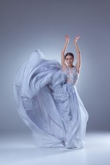 La hermosa bailarina bailando en vestido largo lila sobre fondo lila