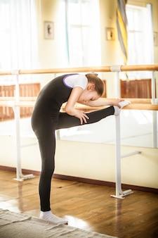 Hermosa bailarina de ballet poco estiramiento en clase de baile