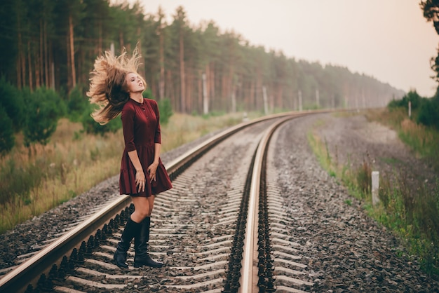 Hermosa bailarina con cabello natural rizado disfrutar de la naturaleza en el bosque en ferrocarril. soñadora dama en vestido burdeos a pie en ferrocarril.