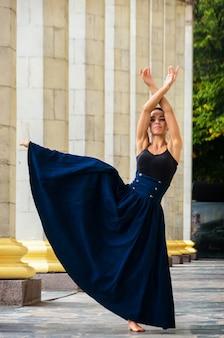 Hermosa bailarina elegante en un top negro y una larga falda azul baila en la calle de la ciudad