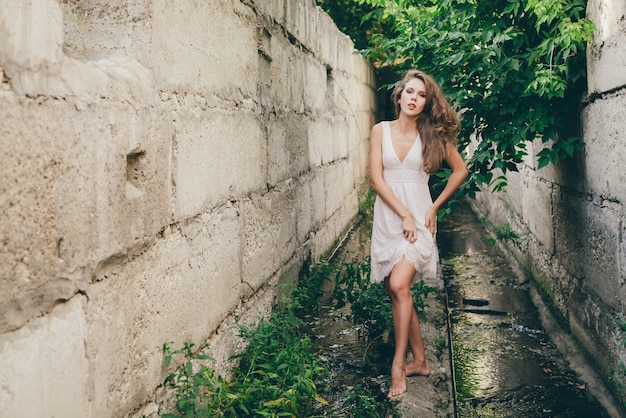 Hermosa bailarina feliz con cabello rizado natural en vestido blanco cerca de hojas de árbol verde