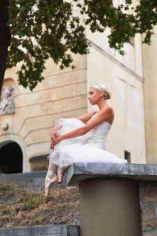 Hermosa bailarina graciosa bailando en las calles de un viejo ci