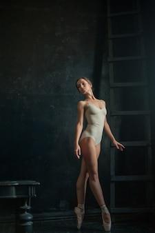 Hermosa bailarina posin en cuarto oscuro