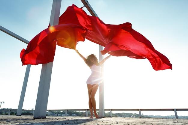 Hermosa bailarina de seda morena con cortinas rojas posando en la azotea