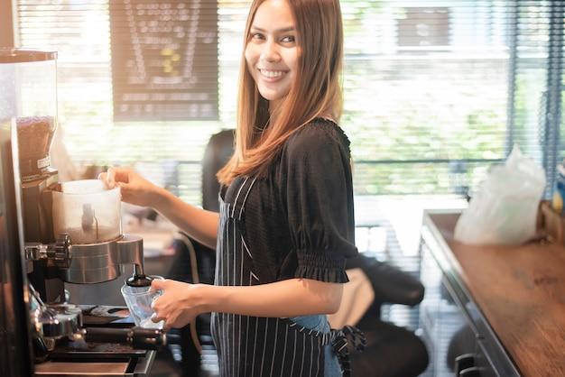 Hermosa barista está sonriendo en su cafetería