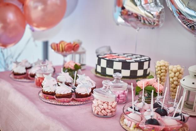 Hermosa barra de caramelo rosa con cupcakes, pops, pastel.