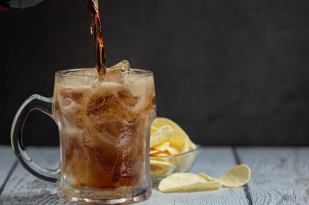 Hermosa bebida fría de cola con cubitos de hielo