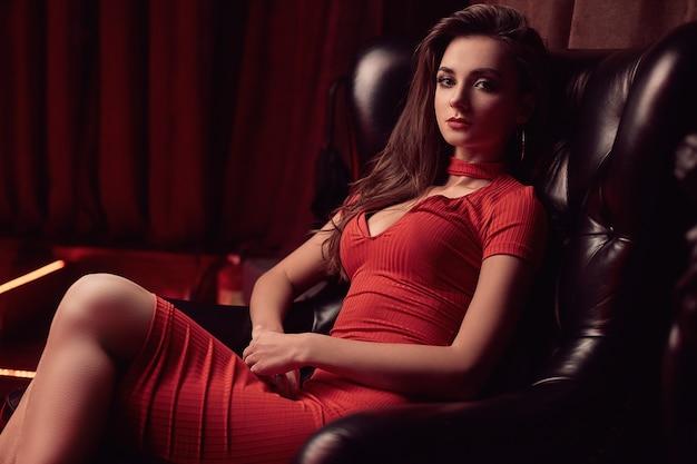 Hermosa belleza joven morena en una silla de cuero