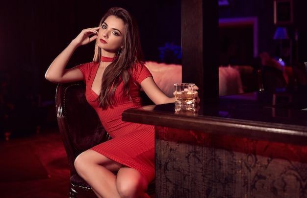 Hermosa belleza joven morena con vestido rojo con vaso de whisky