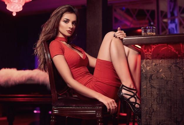 Hermosa belleza joven morena en vestido rojo con vaso de whisky