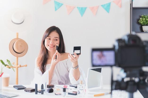 Hermosa blogger de mujer asiática está mostrando cómo maquillar y usar cosméticos.