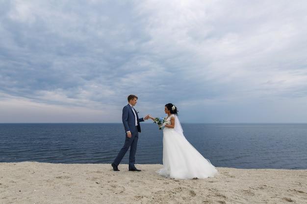 Hermosa boda feliz pareja novia y novio en el día de la boda al aire libre en la playa