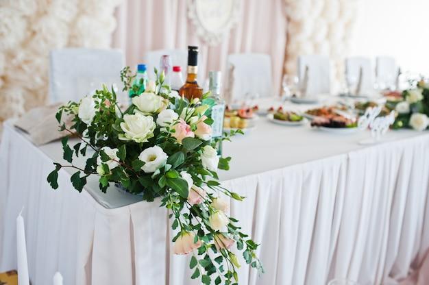 Hermosa boda set decoración en el restaurante. flores en la mesa de recién casados.