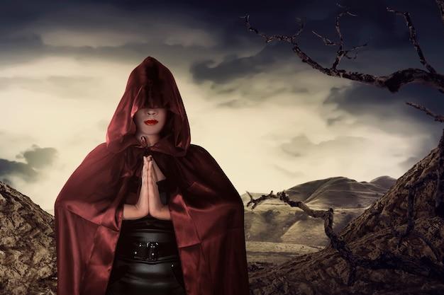Hermosa bruja asiática con manto rojo rezando