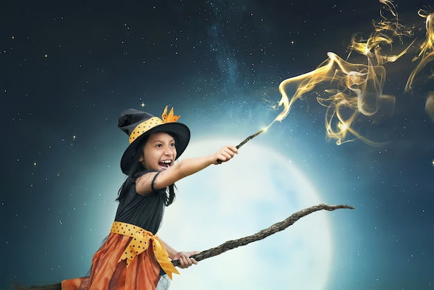 Hermosa bruja asiática usando la varita mágica